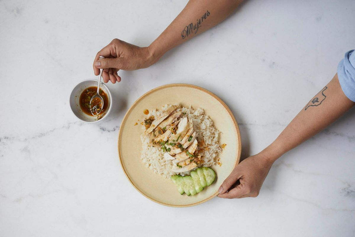 Two hands getting a spoonful of sauce to put over chicken and rice with sliced cucumbers on a marble countertop.