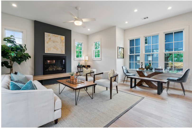 A white living room with a black fireplace and small dining table.