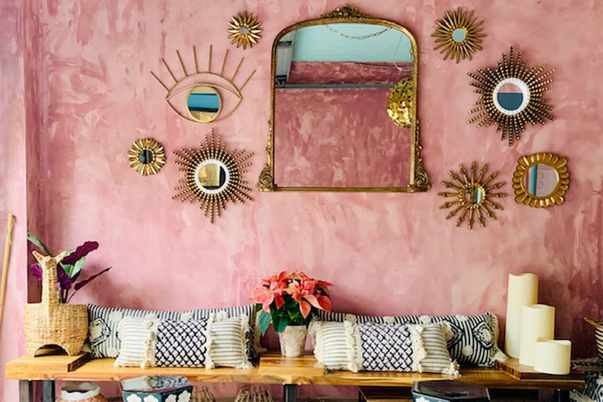 Interior of the wine bar with pink walls, gold mirrors on the walls, white and blue cushions