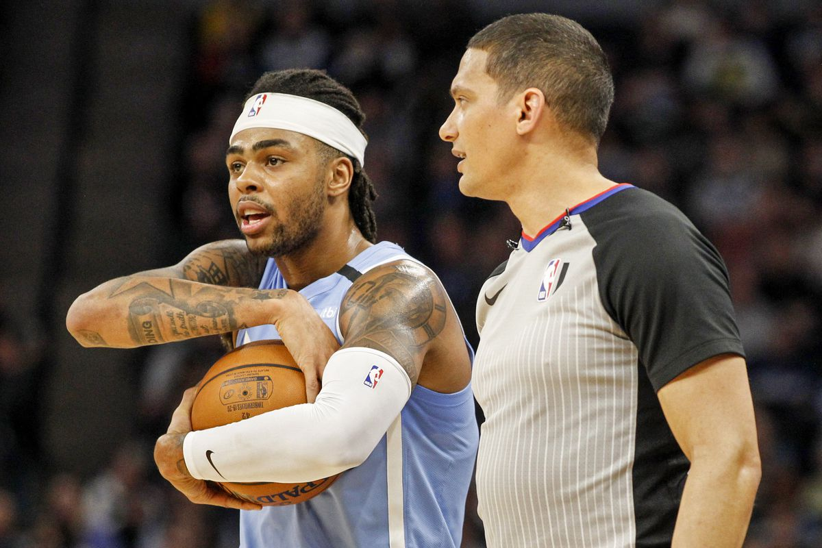 Minnesota Timberwolves guard D'Angelo Russell holds the ball with referee Nate Green as they wait for action to resume in the game with the Boston Celtics head coach Brad Stevens at Target Center.