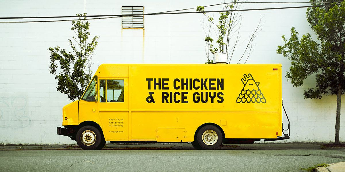 """A yellow food truck is parked in front of a white building. The truck has """"The Chicken & Rice Guys"""" printed on it in a black font, along with a chicken logo."""