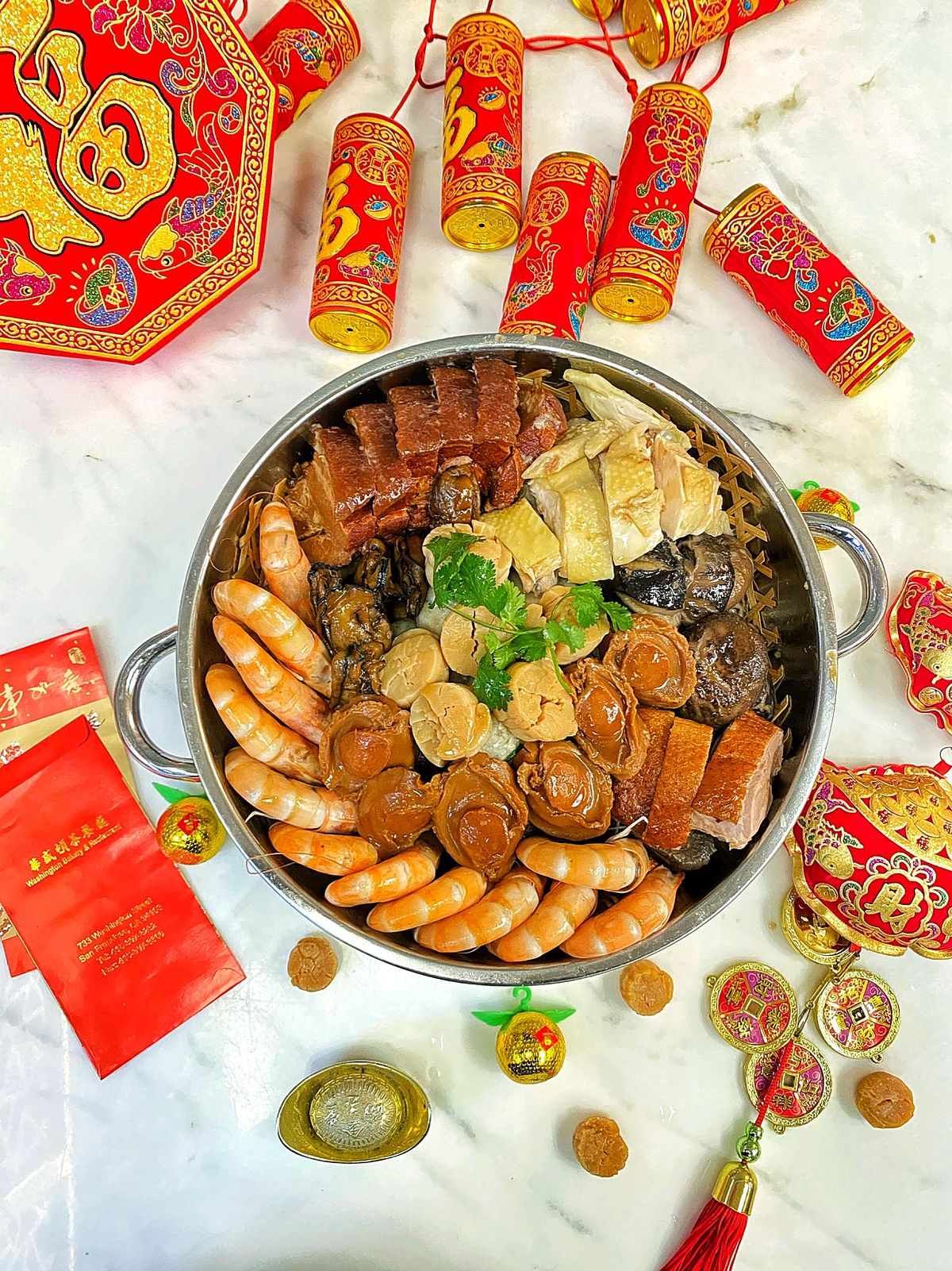 """A celebratory one-pot """"poon choi"""" Lunar New Year meal — a pot loaded with shrimp, abalone, pork belly, and more —with red envelopes and firecrackers scattered alongside on the table"""