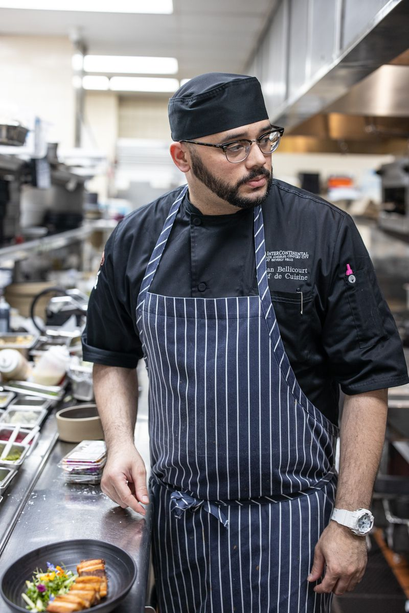 Chef Brian Bellicourt wearing a striped apron standing over the kitchen counter at Mari restaurant in Los Angeles.