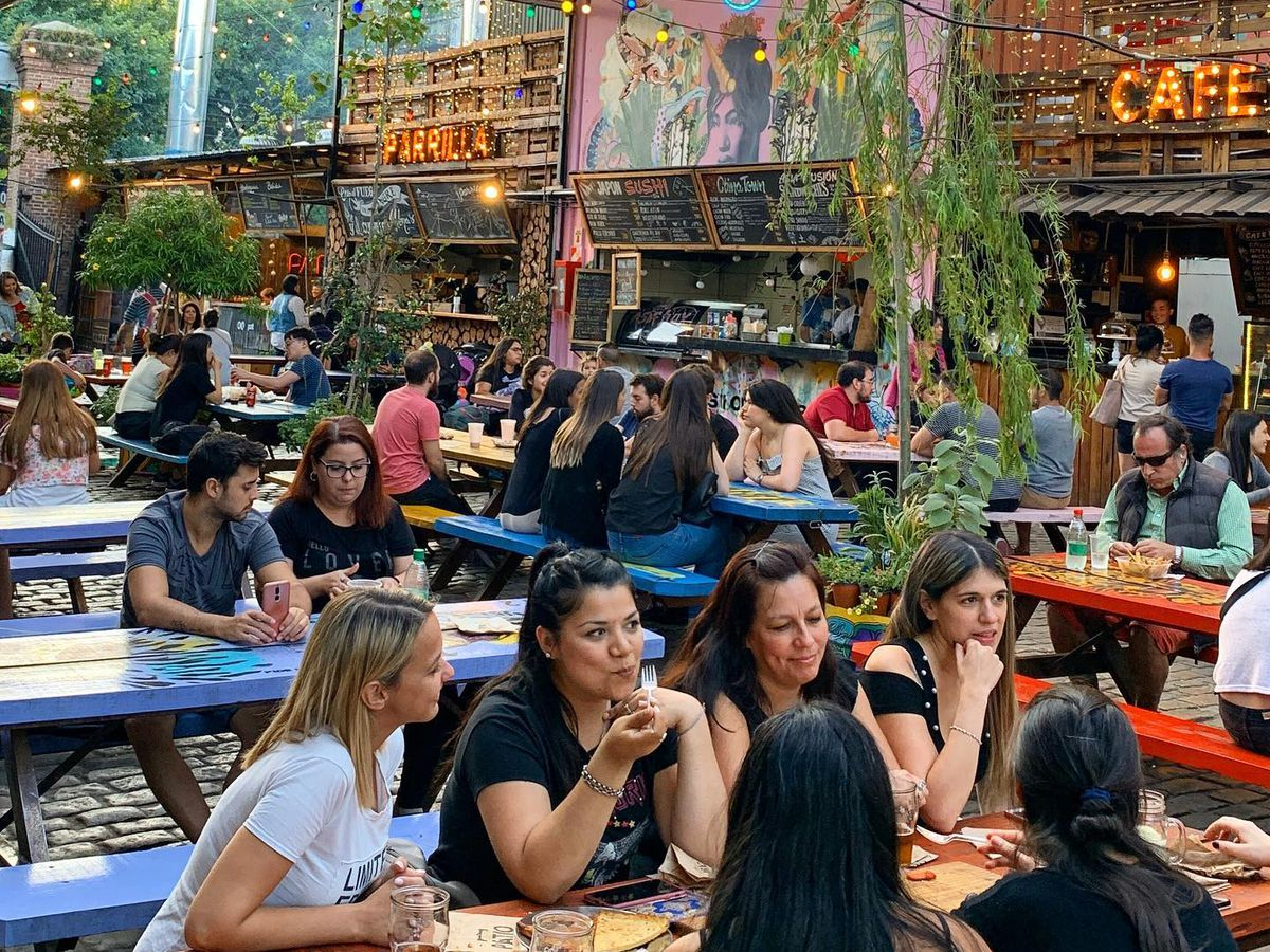 Diners sit at a series of long communal tables beneath a colorful glass ceiling in a wide open food hall