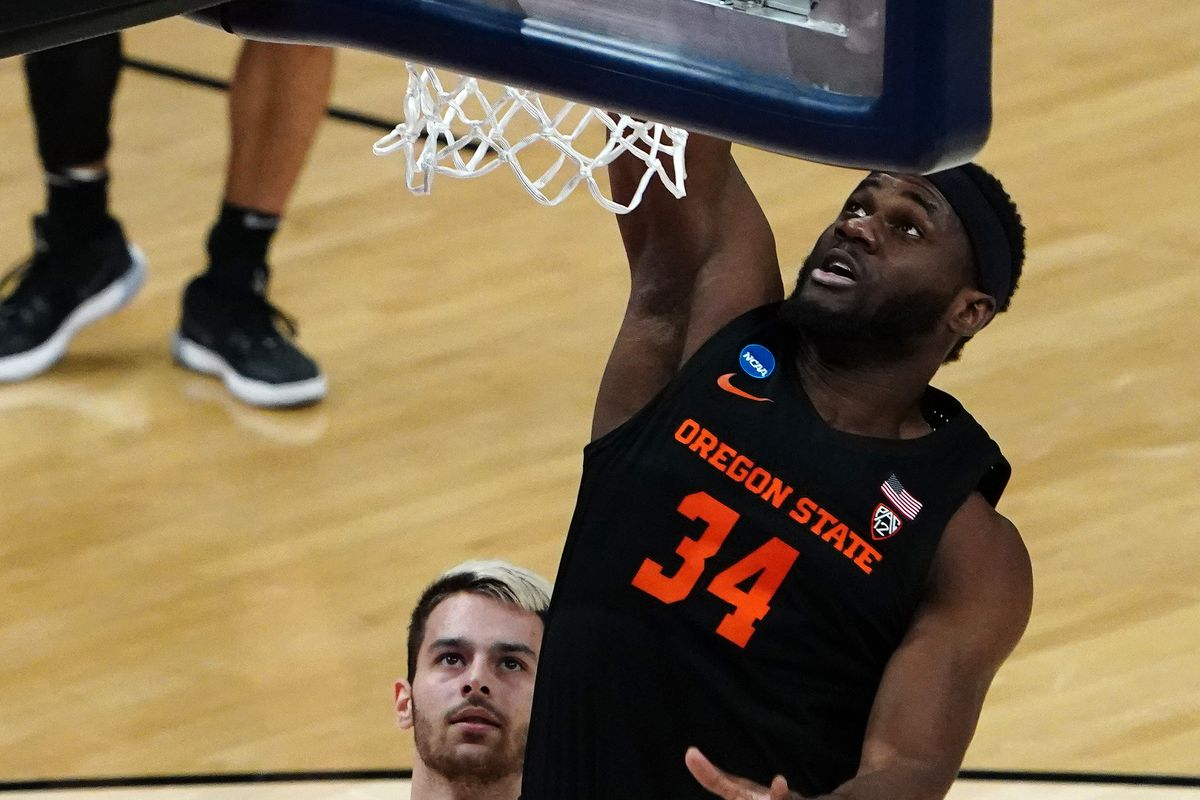 Oregon State Beavers forward Rodrigue Andela (34) dunks the ball as Tennessee Volunteers guard Santiago Vescovi looks on during the first half in the first round of the 2021 NCAA Tournament at Bankers Life Fieldhouse.