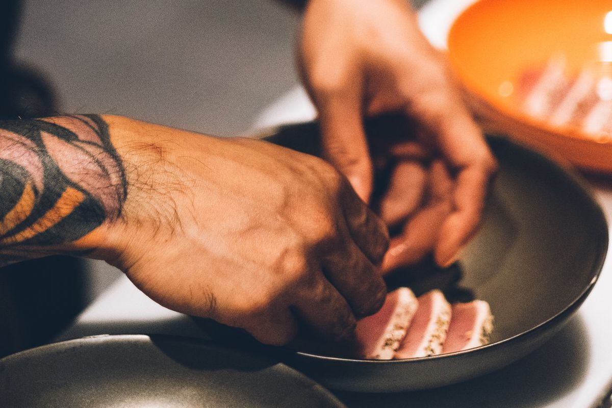 A chef places slices of raw fish into a black bowl.