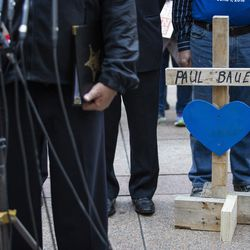 A cross for Chicago Police Cmdr. Paul Bauer by Greg Zanis, of Crosses for Losses, sits behind Supt. Eddie Johnson as he speaks during a press conference outside the Thompson Center in 2018.