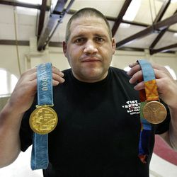 """FILE - In this Feb. 27, 2007, file photo, Rulon Gardner holds his gold and his bronze Olympic medals after giving a motivational talk to students and faculty at the Middlesex School in Concord, Mass. The auction of Olympic gold medalist Rulon Gardner's most valuable belongings is being postponed indefinitely as the decorated wrestler tries to buy back """"stuff that really matters to him,"""" his new bankruptcy lawyer says. A major creditor seized a Ford Excursion SUV, Harley-Davidson motorcycle, dozens of watches and knives, his wrestling shoes, autographed memorabilia and more. Gardner's gold and bronze medals are not in play; he previously put them up as collateral for personal loans.  (AP Photo/Michael Dwyer, File)"""