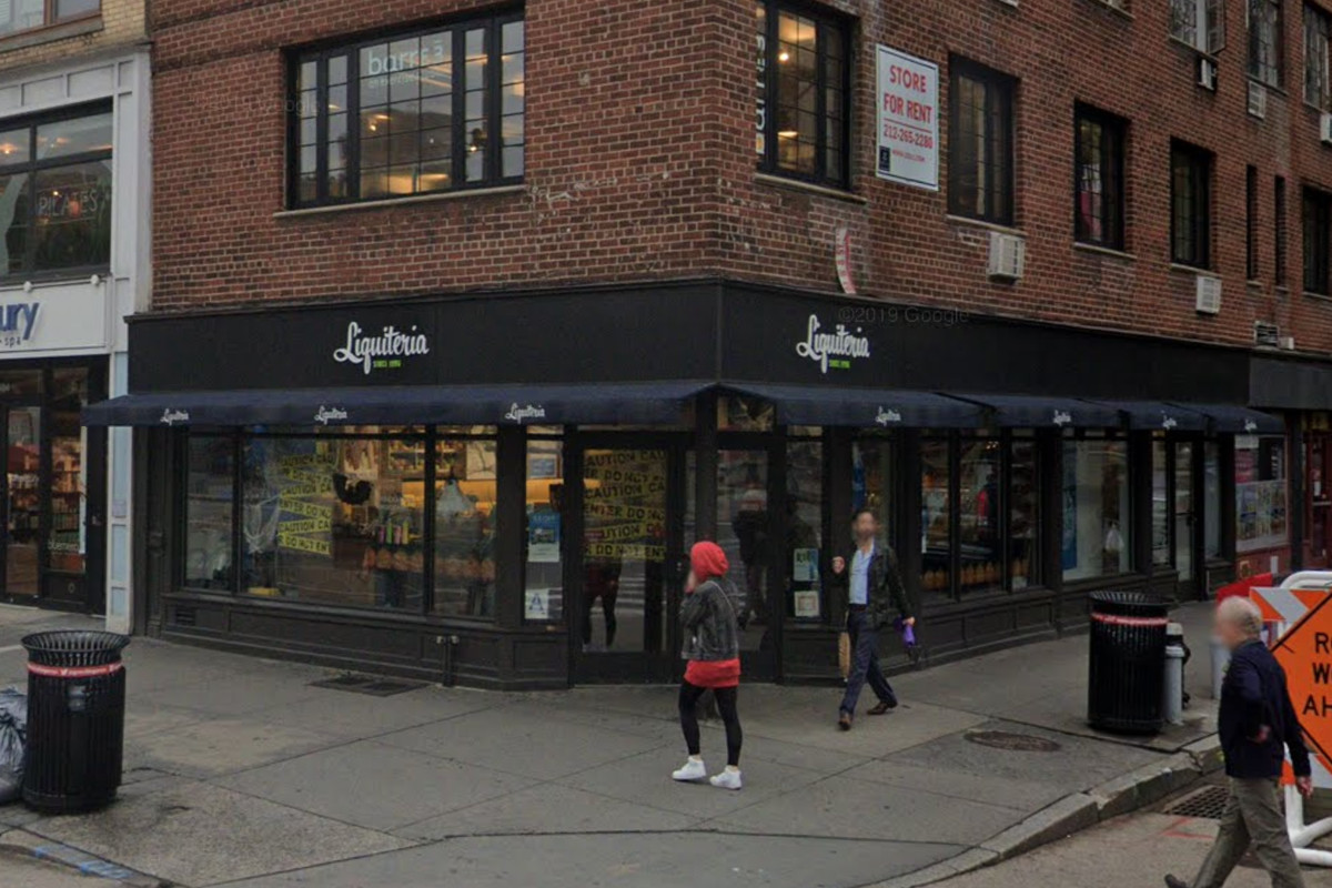 The exterior of a storefront that has blue signage that reads Liquiteria