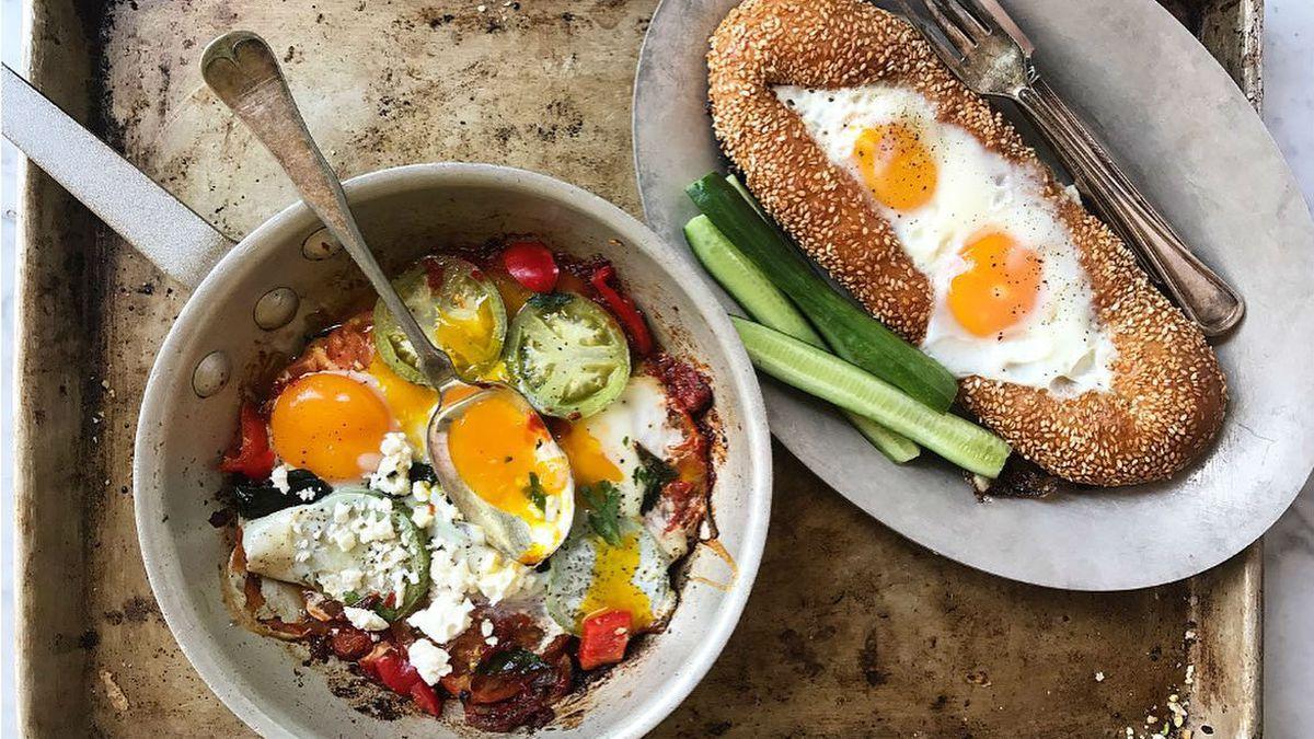 Overhead view of shakshuka and an egg-filled Jerusalem bagel