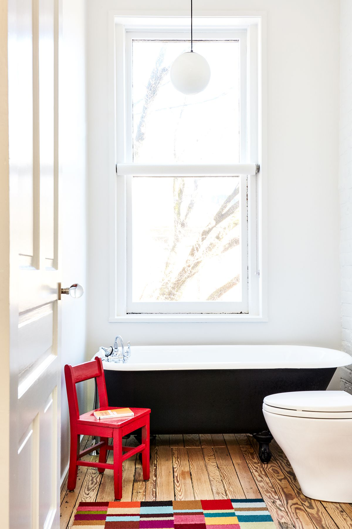 A bathroom. There is a bathtub with a black exterior and white interior. A red chair is next to the tub. There is a large window over the tub. The walls are painted white.
