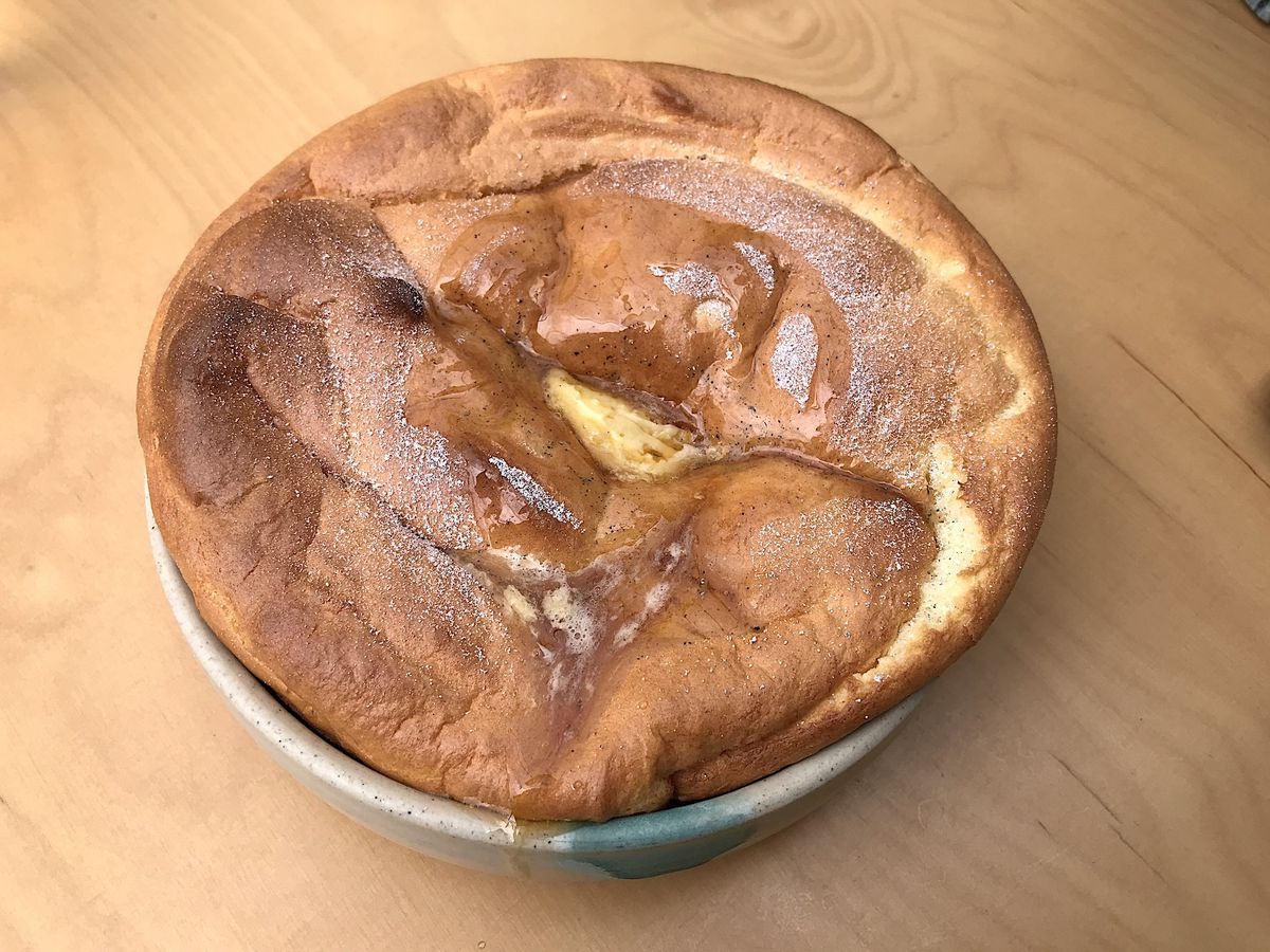 A deflated but golden brown souffle rests in a tin dish on top of a wooden table