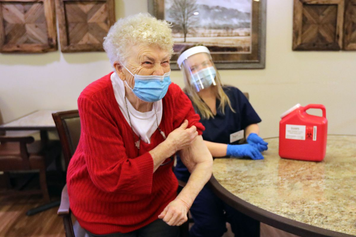 Phyllis Patrick, 84, pulls down her sleeve and smiles after getting vaccinated for COVID-19 by CVS pharmacist Angela Nhan at Summit Senior Living in Kearns on Thursday, Jan. 14, 2021.