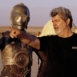 """In this undated publicity photo released by Lucasfilm Ltd. & TM, director George Lucas directs actor Anthony Daniels, who plays the robot C-3PO, in """"Star Wars II: Attack of the Clones,"""" on location in the Tunisian desert."""