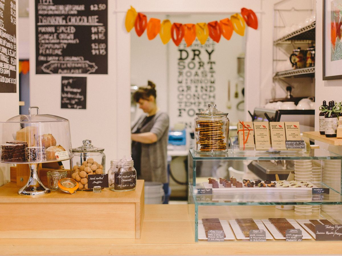 A coffee counter, with a pastry case and other treats, blackboard menus, and a barista at work in a rear room