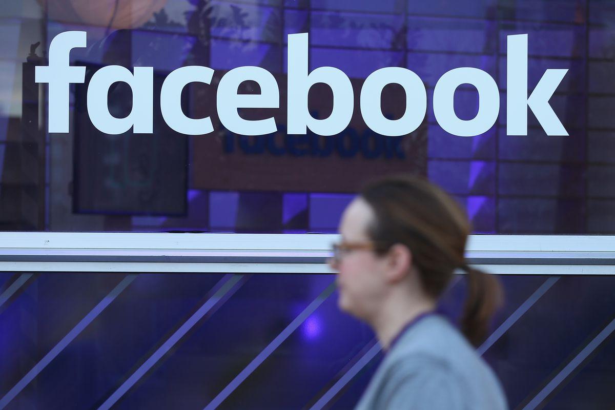 A woman walks past a Facebook sign