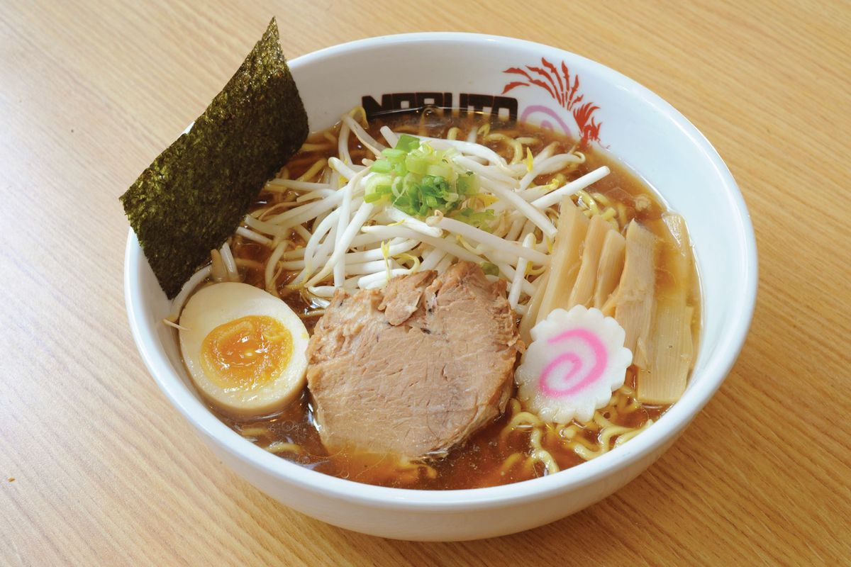 A bowl of ramen with soup, noodles, bean rpouts, greens, a slice of pork, a half-sliced hard-boiled egg, a fish cake with a pink swirl, and a slice of seaweed