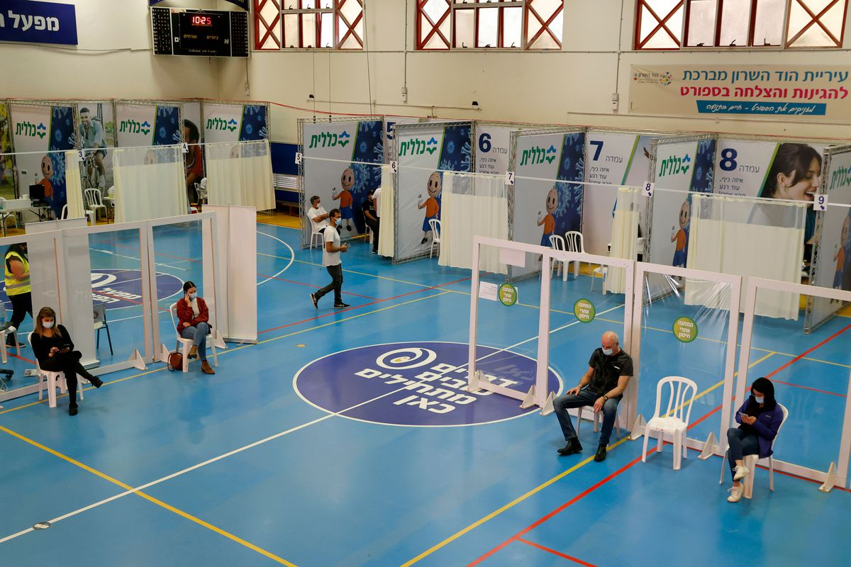 People waiting to be inoculated sit distanced from one another in a gymnasium being used as a vaccination center.