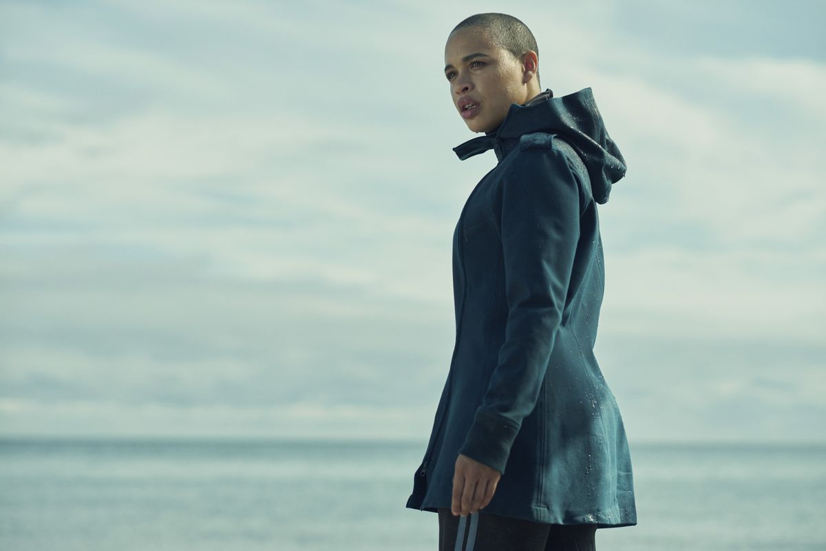 a young woman with a shaved head and a blue coat stands in front of the sea, she looks shocked