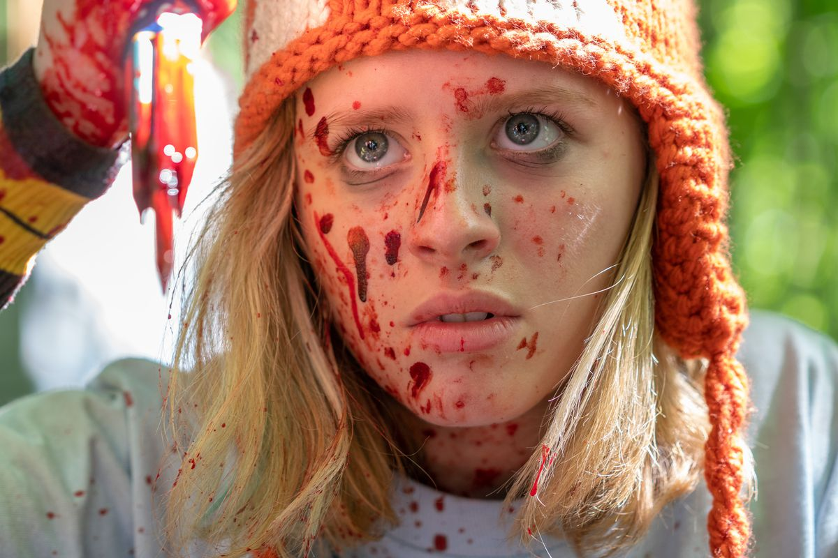 A close-up of the blood-spattered face of a young blonde woman in a knit hat, holding up in an unclear, blurry, bloody weapon in the foreground.