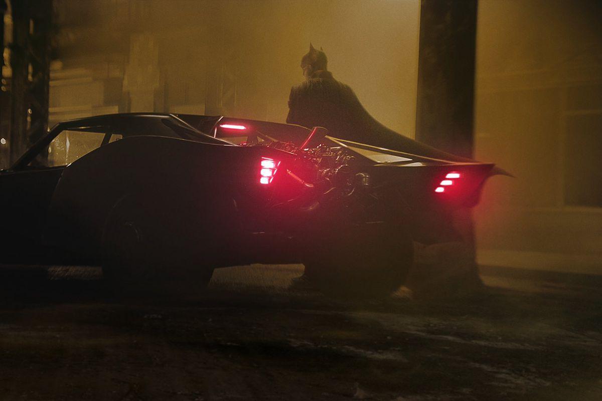 Robert Pattinson as Batman stands next to his black Batmobile in a still from The Batman (2021)