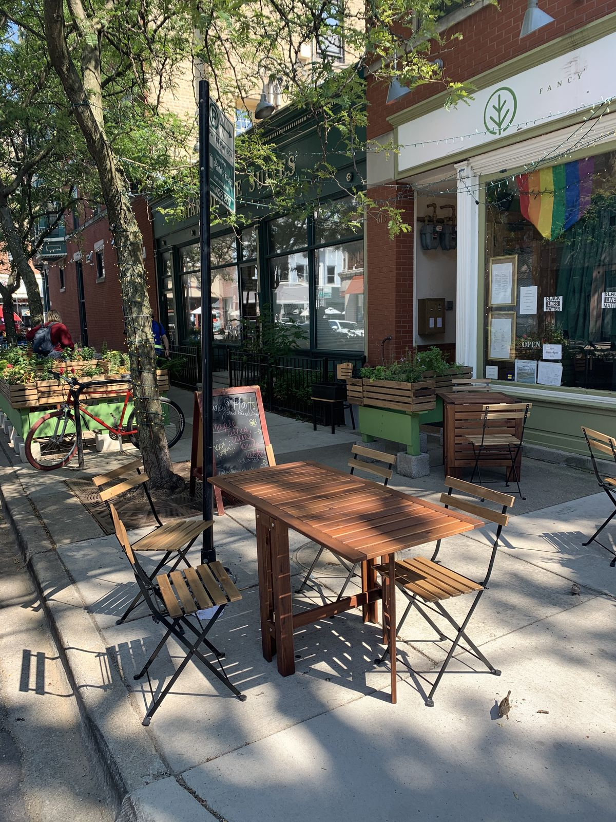 A sidewalk cafe on a tree-lined street during the day.