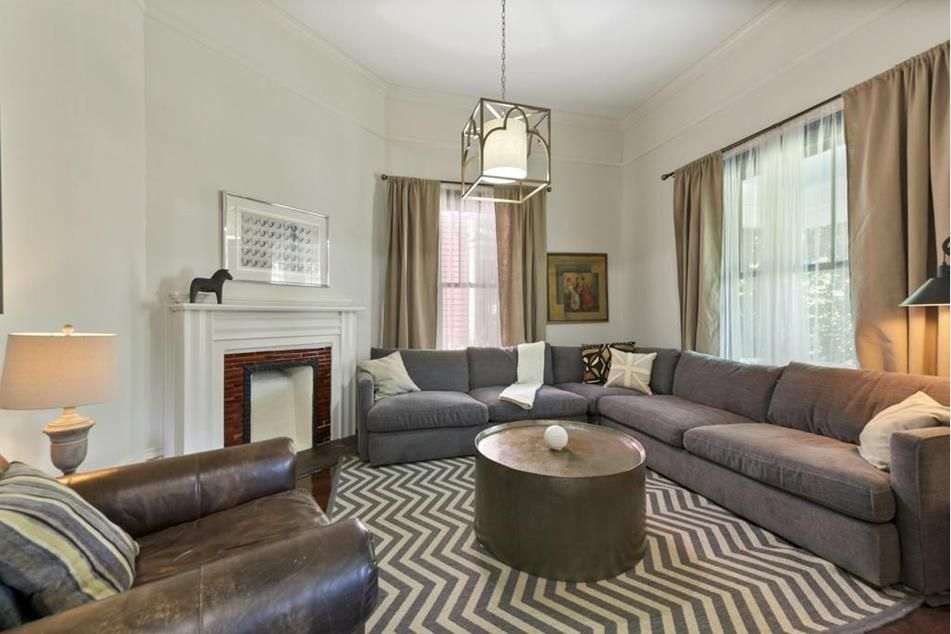 A big white living room with a gray couch.