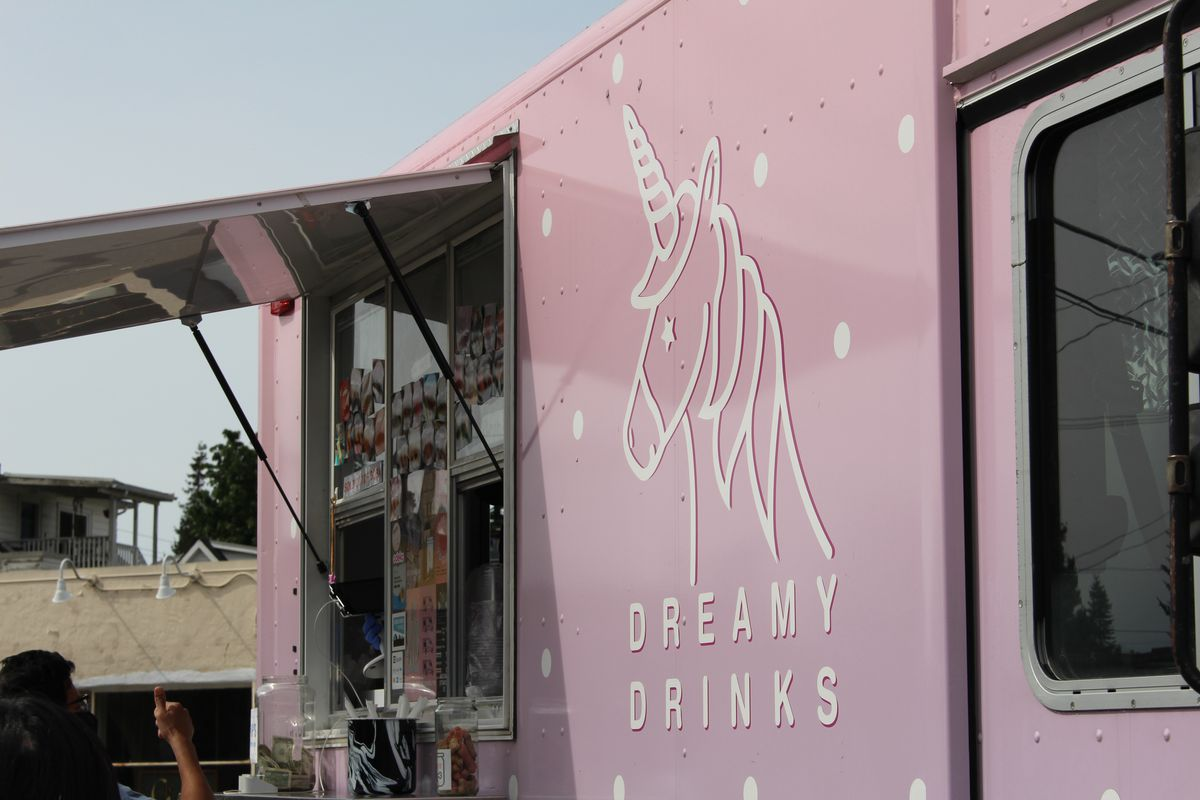 The pink facade of the Dreamy Drinks boba tea/food truck, with the business's name on the front underneath a logo of a unicorn traced in white.