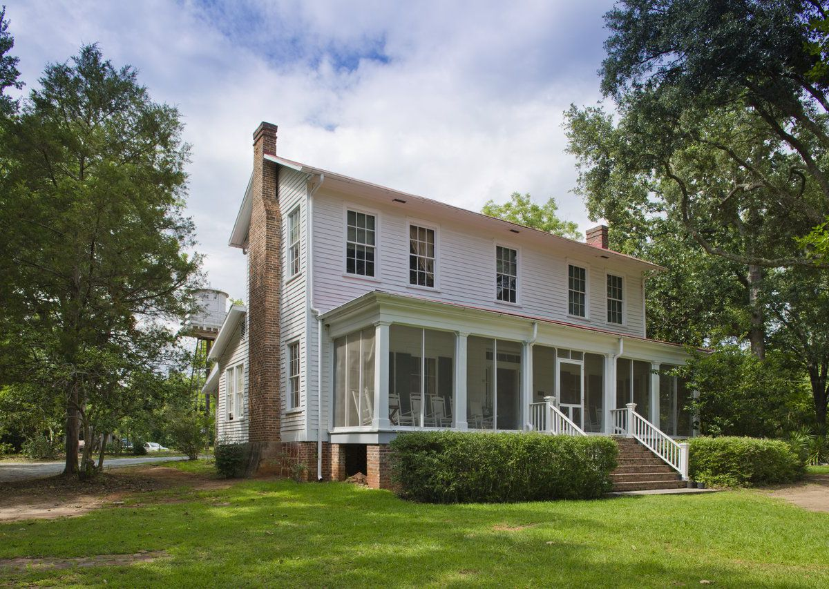 The exterior of Andalusia in Atlanta. The facade is white with a veranda and columns. There is a red brick chimney.