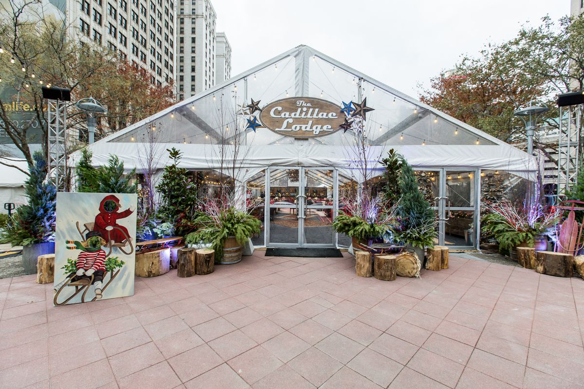 A larger glass shed with holiday planters outside.
