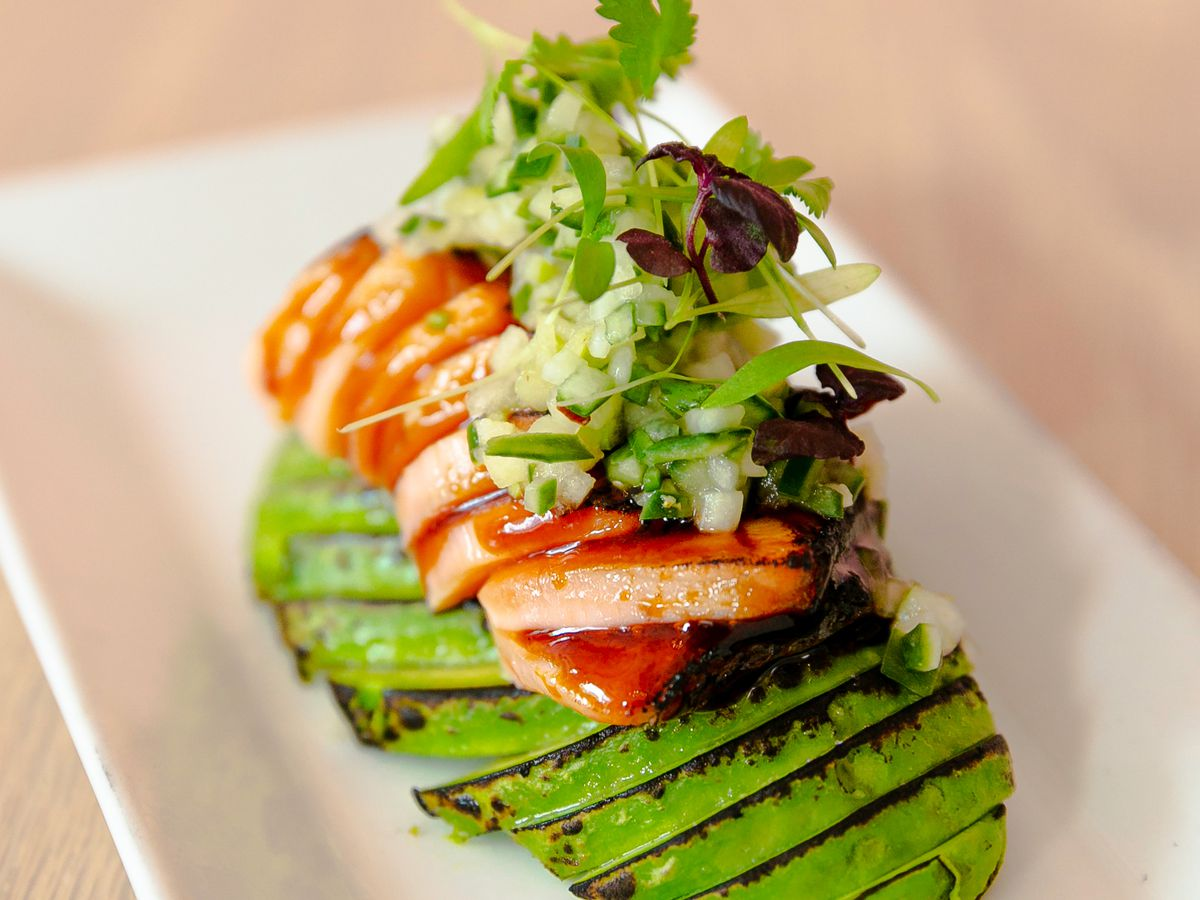 Slices of torched salmon sit atop slices of charred avocado on a rectangular white plate. It's all topped with microgreens.