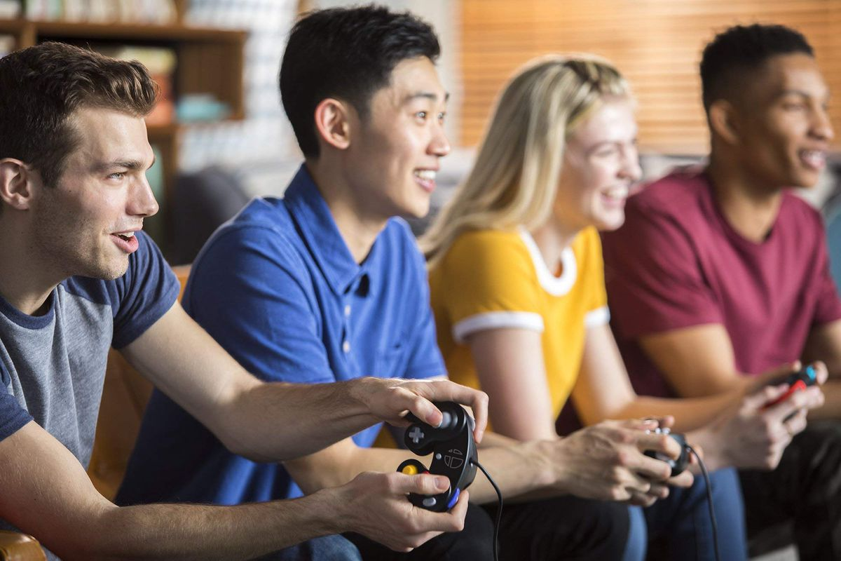 four people playing Super Smash Bros. with GameCube controllers