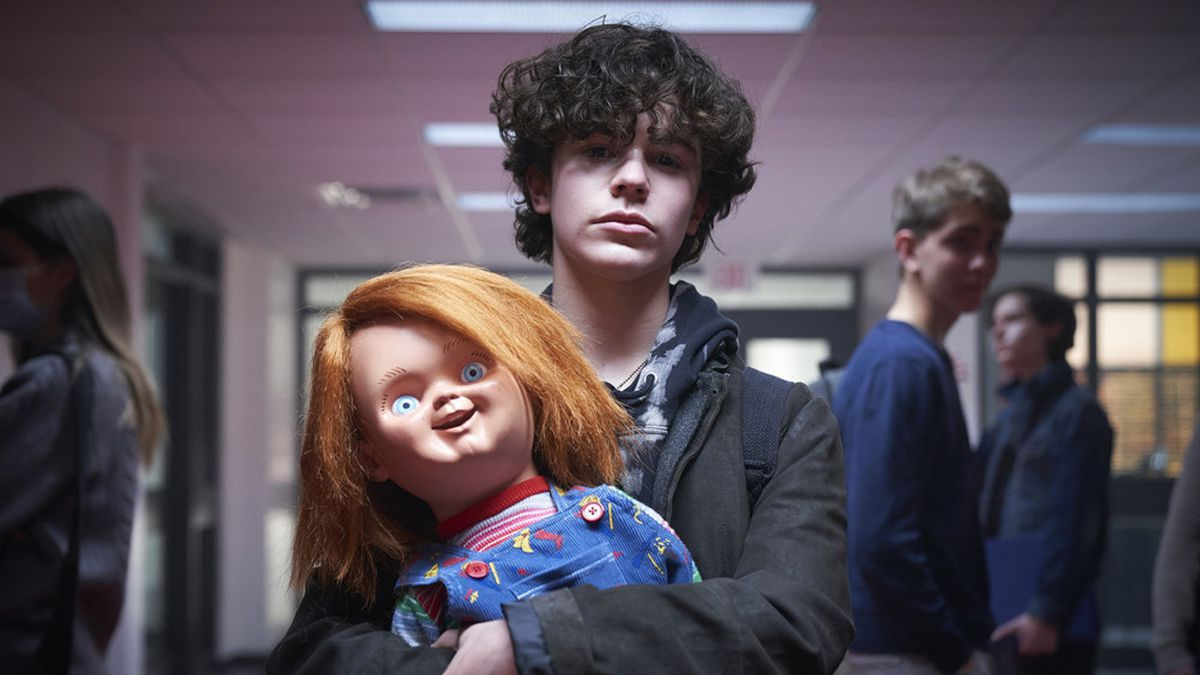 Zackary Arthur holds a beaming Chucky doll in Syfy/USA's horror series Chucky