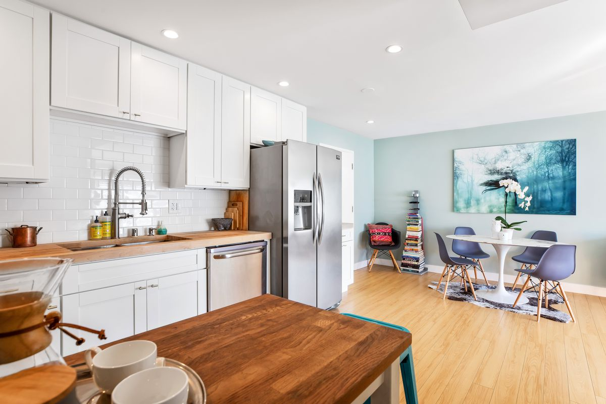 An open concept kitchen with white cabinets and wood floors. A dining table in the background.