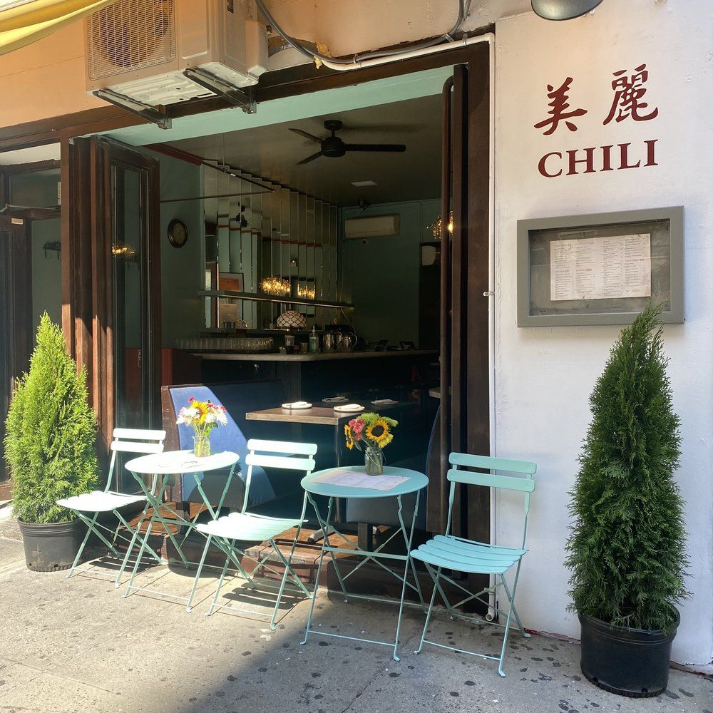 """A restaurant with white tables, chairs, and an open exterior with the words """"Chili"""" in red font besides Chinese characters"""