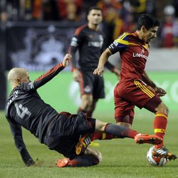 Toronto FC midfielder Michael Bradley (4) tries to kick the ball out of the control of Real Salt Lake defender Tony Beltran (2) during a game at Rio Tinto Stadium in Sandy on Saturday, March 29, 2014.