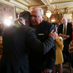 United States Ambassador to Russia Jon M. Huntsman, Jr., left, hugs his father, Jon M. Hunstman, Sr., after a ceremonial swearing-in at the Utah State Capitol in Salt Lake City on Saturday, Oct. 7, 2017. Arizona State won the game, 30-10.