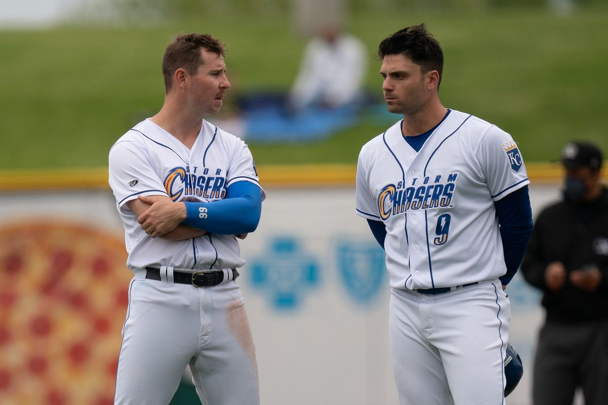 Two baseball players in white Omaha Storm Chasers uniforms stand facing partway toward each other.
