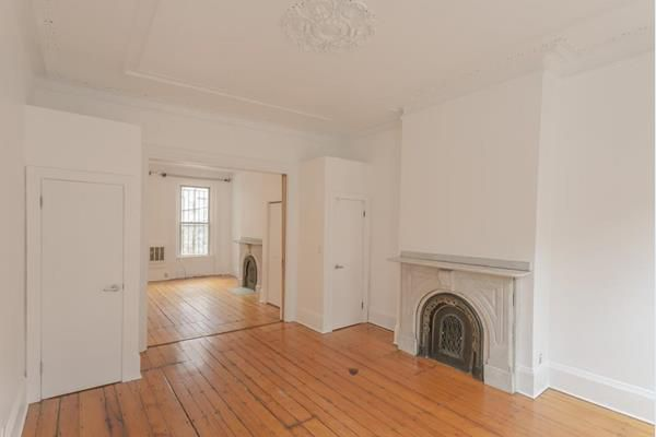 An empty living room with a fireplace, and there's a wide hallway leading off the living room.