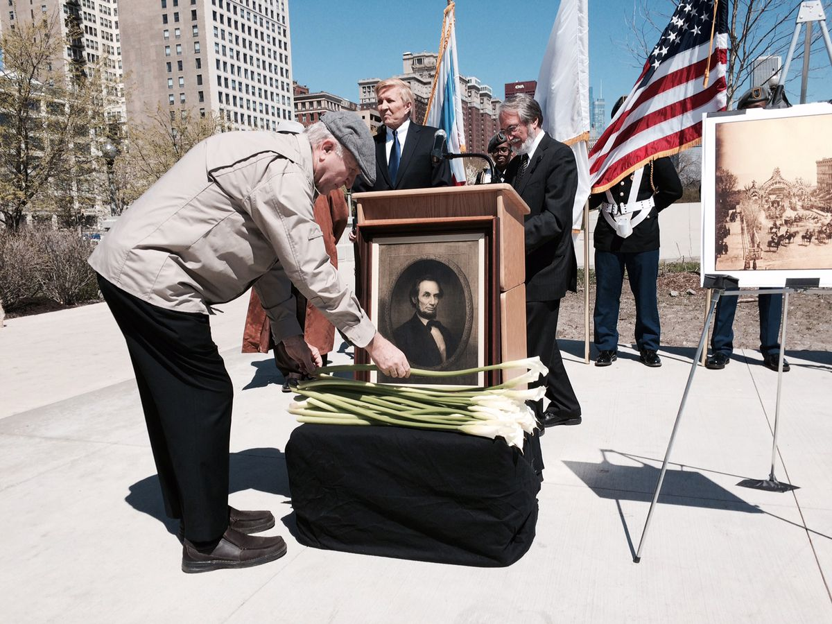 <small><strong>A visitor places lilies below a portrait of Lincoln at the Grant Park ceremony.   Stefano Esposito/Sun-Times</strong></small>