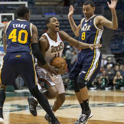 Milwaukee Bucks' Brandon Knight, center, is fouled by Utah Jazz Diante Garrett, right, with teammate Jeremy Evans, left, during the first half of an NBA basketball game Monday, March 3, 2014, in Milwaukee. (AP Photo/Tom Lynn)