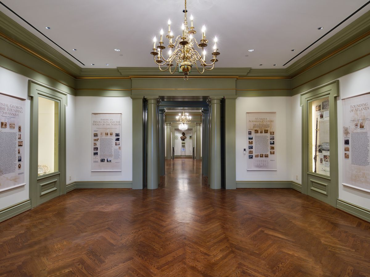 A gallery room with hardwood floors, a large brass chandelier, and informative displays on the walls.
