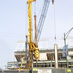 Triangle lot: steel beam being lowered into the ground
