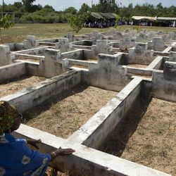 A grieving relative sings along beside unmarked graves, as Catholic priests offer prayers for victims of the 2002 Joola ferry disaster, at a cemetery containing 140 unmarked graves in Mbao, outside Dakar, Senegal, Wednesday, Sept. 26, 2012, the tenth anniversary of the ferry's sinking. With an official death toll of 1,863 and only 64 survivors, the Joola disaster remains one of the deadliest in maritime history, surpassing by a large margin the death toll of roughly 1500 in the 1912 sinking of the Titanic.