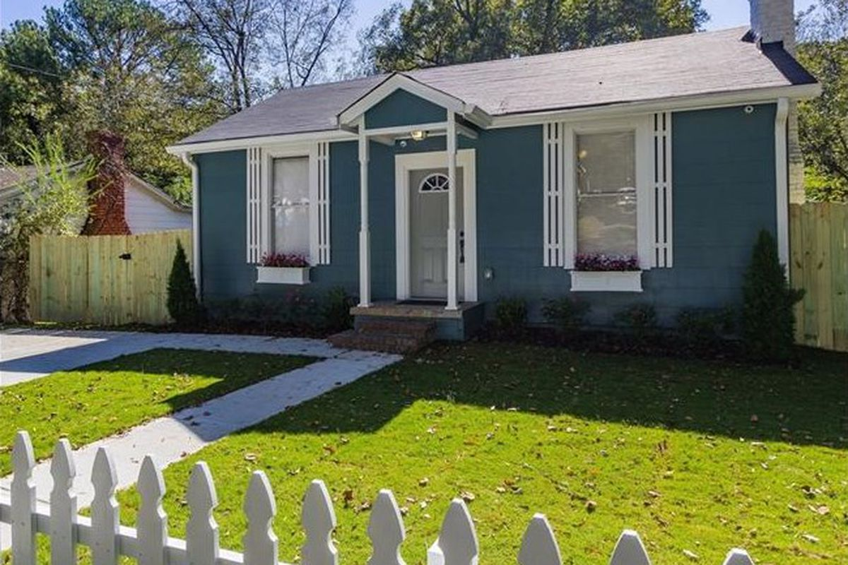 White picket fence by green grass leading to blue house.
