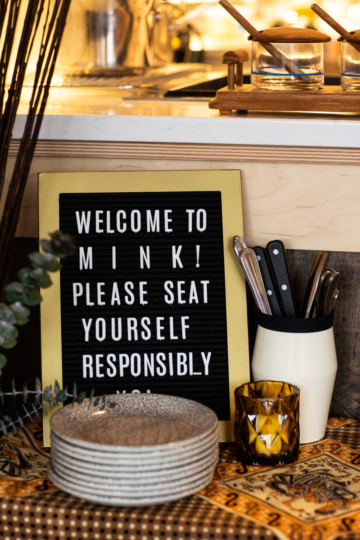 """A sign that says """"Welcome to Mink! Please seat yourself responsibly"""" sits on a table near the entrance to the restaurant."""