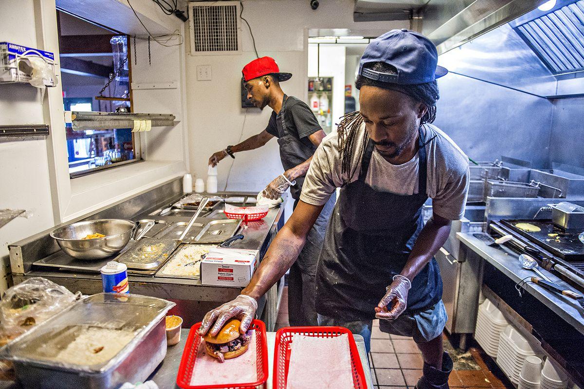 Pitmaster Bryan Furman loads up a chopped whole-hog sandwich in the kitchen.