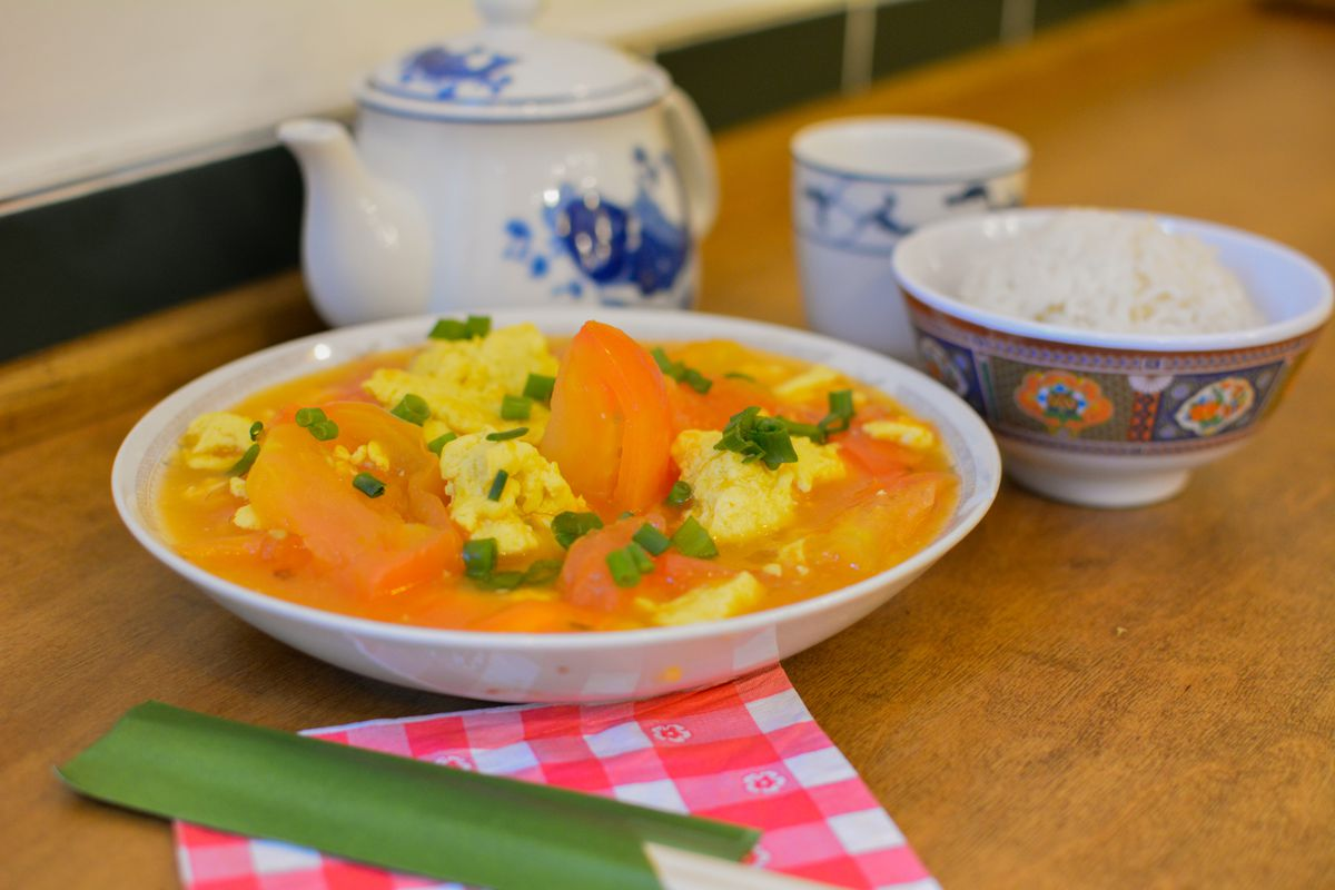 A plate of tomato and egg, with a bowl of rice next to it.