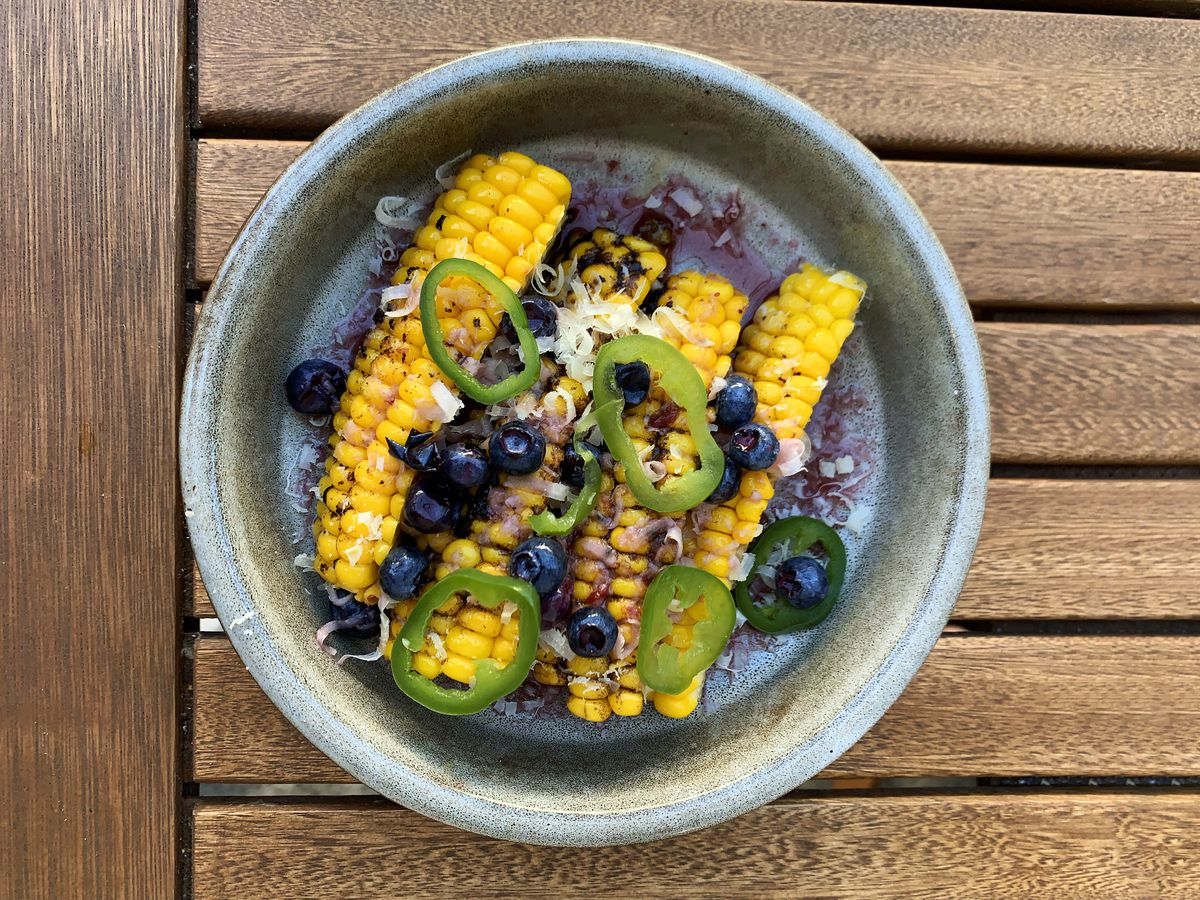 Four pieces of corn ribs with sliced serranos, blueberries, and a purple sauce sit on a plate at Canard in Portland, Oregon