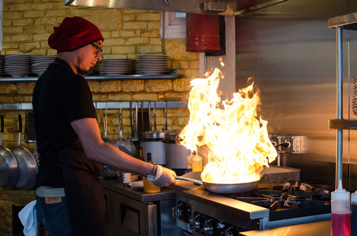 A chef in a black t-shirt and maroon beanie stands at a stovetop with a pan full of flames rising two feet in the air